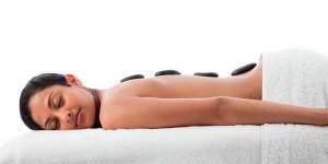 девушка лежит с лечебными камнями на спине