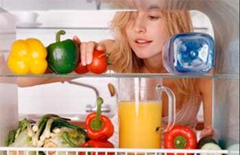 Девушка заглядывает в холодильник